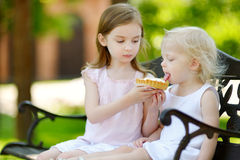 Two little sisters sharing delicious cream tart Royalty Free Stock Images