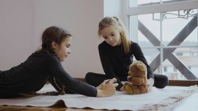 Two girls photographs teddy bear. Two little sisters sits on the floor in the room near the window and relaxing. Cute children plays with phone and photographs stock footage