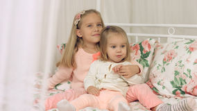 Two little sisters sitting on the couch Royalty Free Stock Photography
