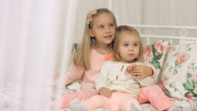 Two little sisters sitting on the couch Royalty Free Stock Photo