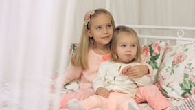 Two little sisters sitting on the couch Royalty Free Stock Photos