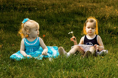 Two little sisters sitting in the grass Royalty Free Stock Photos