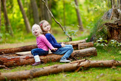 Two little sisters sitting on a log in a forest Royalty Free Stock Photo