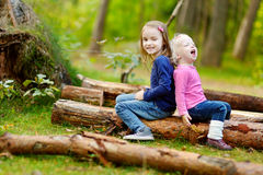 Two little sisters sitting on a log in a forest Stock Photography