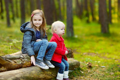 Two little sisters sitting on a log in a forest Stock Photo