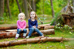 Two little sisters sitting on a log in a forest Royalty Free Stock Images