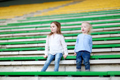 Two little sisters sitting on a stadium seats Royalty Free Stock Images