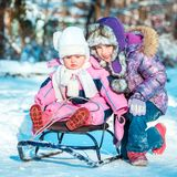 Two little sisters on a sled Stock Image