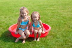 Two little sisters in small pool have fun Stock Images