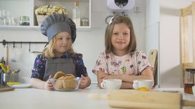 Two little sisters smiling with homemade cookies and cups of tea at cooking studio. Horizontal Royalty Free Stock Photography