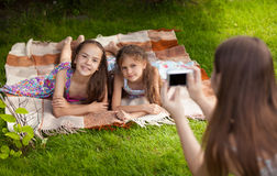 Two little sisters smiling for photo while having fun on grass Stock Images