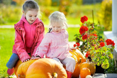 Two little sisters and some huge pumpkins Stock Photo
