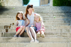 Two little sisters and their mom having fun together Stock Photography