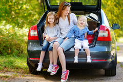 Two little sisters and their mother in a car. Two adorable little sisters and their mother sitting in a car just before leaving for a car vacation Royalty Free Stock Photo
