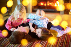 Two little sisters and their mother enjoying their time together on Christmas morning Stock Photography