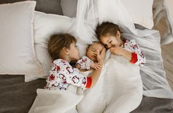 Two little sisters and a tiny brother lie on the bed under the white blanket in the light cozy bedroom.  royalty free stock images