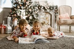 Two little sisters and a tiny brother lie on the carpet and read book near the New Year`s tree with gifts in the light. Cozy room with armchair and fireplace royalty free stock images