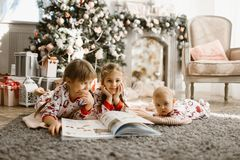Two little sisters and a tiny brother lie on the carpet and read book near the New Year`s tree with gifts in the light. Cozy room with armchair and fireplace stock photo