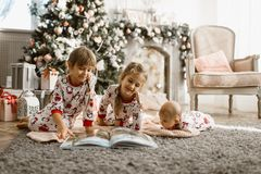 Two little sisters and a tiny brother lie on the carpet and read book near the New Year`s tree with gifts in the light. Cozy room with armchair and fireplace royalty free stock photos