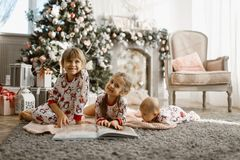 Two little sisters and a tiny brother lie on the carpet and read. Book near the New Year`s tree with gifts in the light cozy room with armchair and fireplace royalty free stock photo