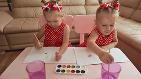 Two little sisters twins are happy to paint drawings with watercolors sitting at the table together. Two little sisters twins are happy to paint drawings with stock footage