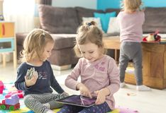 Two little sisters use tablet at home stock photography