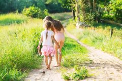 Two little sisters walking and playing on the road in countryside on a warm summer sunset. Cute little girls. Back view royalty free stock photo