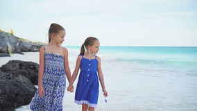 Two little sisters walking by the sea on the white beach. Little girls having fun at tropical beach during summer vacation playing together at shallow water stock footage