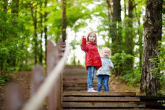 Two little sisters walking up stairs. In summer park on beautiful sunny day Stock Photos
