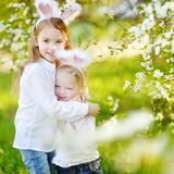 Two little sisters wearing bunny ears on Easter Stock Photo