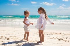 Two little sisters in white clothes have fun at Stock Photos