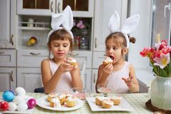 Two little sisters with white rabbit`s ears on their heads eat small Easter cakes in the cozy light kitchen.  stock photo