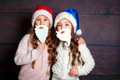 Two little smiling girls having fun .Christmas concept. Smiling funny sisters in Santa hat on wooden background. Two happy little smiling girls having fun Stock Image