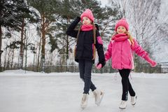 Two Little smiling girls skating on ice in pink wear. Stock Image