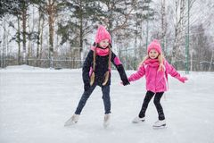 Two Little smiling girls skating on ice in pink wear. Stock Photo