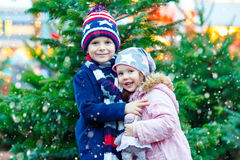 Two little smiling kids, boy and girl with christmas tree Stock Photo