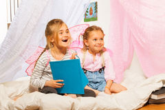 Two little smiling pixies reading the fairy-tale Royalty Free Stock Photo