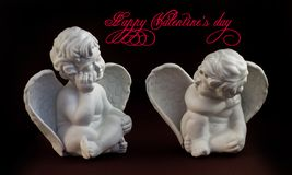 Two little stone angels sitting opposite each other royalty free stock image