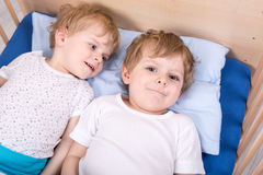 Two little toddler boys having fun in bed Royalty Free Stock Photography