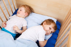 Two little toddler boys having fun in bed Stock Photos