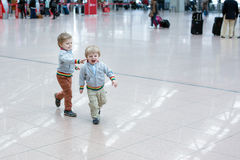 Two little toddler boys playing at the airport Stock Photos