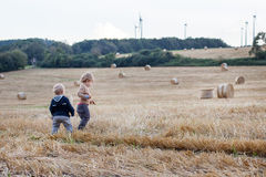 Two little toddler boys playing on straw field Royalty Free Stock Photos