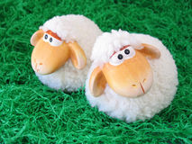 Two little toy sheeps. On green grass background Stock Photos