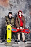 Two little twin boys in casual clothes with skateboards in studio. Teen and kids fashion concept. Two little twin brothers in casual clothes with skateboards in stock photo