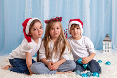 Two little twin brothers and their big sister, Christmas concept Royalty Free Stock Photo