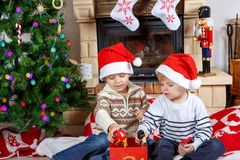 Two little twin kids being happy about christmas presents Stock Photos