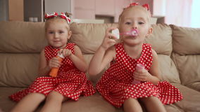 Two little twin sisters in charming red dresses are blowing soap bubbles cheerfully while sitting in the room barefoot. stock video footage