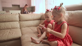 Two little twin sisters in charming red dresses are blowing soap bubbles cheerfully while sitting in the room barefoot. Two little twin sisters in charming red stock video