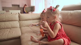 Two little twin sisters in charming red dresses are blowing soap bubbles cheerfully while sitting in the room barefoot. Two little twin sisters in charming red stock video footage