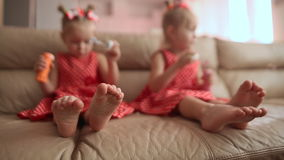 Two little twin sisters in charming red dresses are blowing soap bubbles cheerfully while sitting in the room barefoot. View with emphasis on legs stock video
